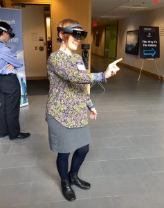 Photo of a person eewearing a Microsoft Hololens display and pointing with one finger
