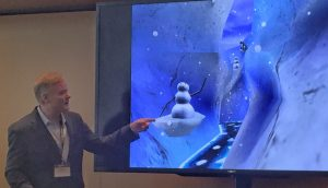 Photo pf a man pointing to a screen with an image of a virtual world called SnowWorld